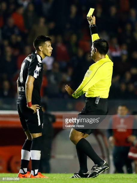 Referee Enrique Cáceres shows the yellow card to Maximiliano Eduardo Meza of Independiente during the first leg match between Independiente and...