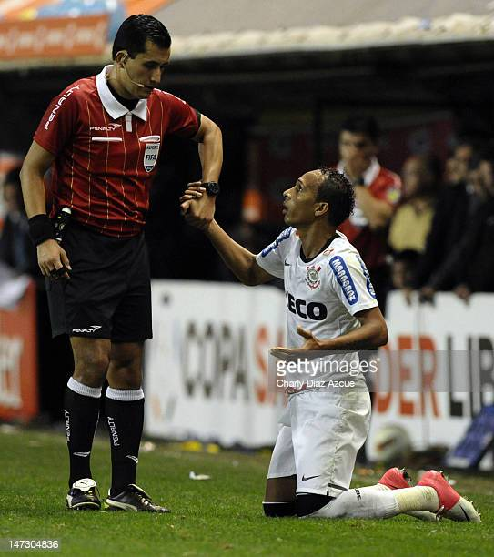 Referee Enrique Osses of Chile helps Liedson of Corinthians during a match between Boca Juniors and Corinthians as part of the first leg of the...