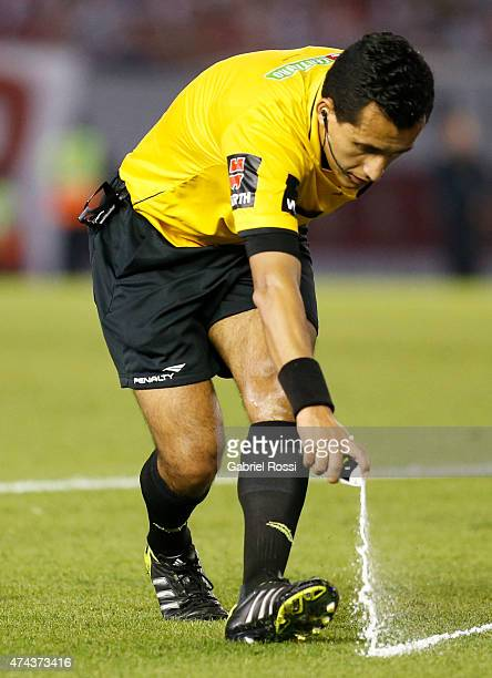 Referee Enrique Osses of Chile sprays vanishing foam to mark out the proper distance before a free kick during a first leg match between River Plate...