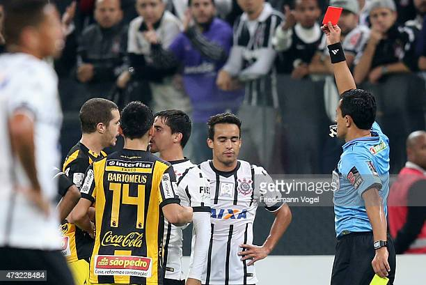 Referee Enrique Osses shows Jadson of Corinthians the yellow card during a match between between Corinthians and Guarani as part of round of sixteen...
