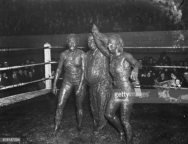 Referee Ernie Maddock raises the hand of Mildred Burke after Miss Burke claimant to the Women's World Wrestling Championship has scored a onefall...
