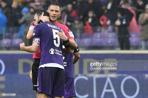 Referee Fabrizio Pasqua comforts Fiorentina's midfielder and new captain Milan Badelj on March 11 2018 at the end of the Italian Serie A football...