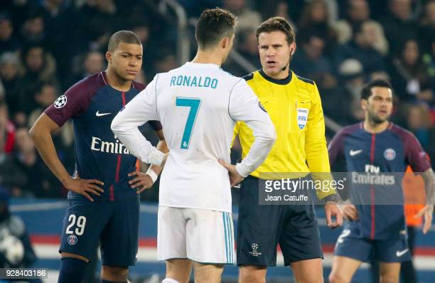 Referee Felix Brych of Germany talks to Cristiano Ronaldo of Real Madrid while Kylian Mbappe of PSG looks on during the UEFA Champions League Round...