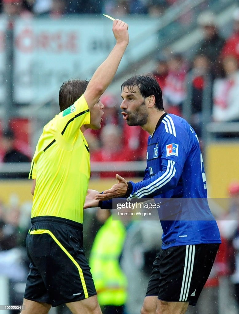 Referee Felix Brych (L) showes the yellow card to Ruud van Nistelrooy (R) of Hamburg during the Bundesliga match between FSV Mainz 05 and Hamburger SV at Bruchweg Stadium on October 16, 2010 in Mainz, Germany.
