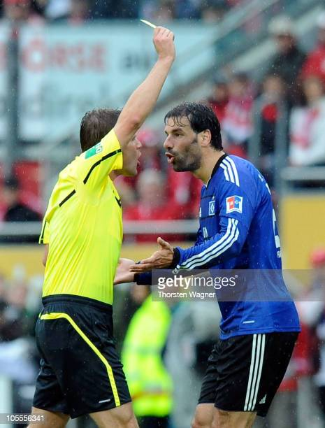 Referee Felix Brych showes the yellow card to Ruud van Nistelrooy of Hamburg during the Bundesliga match between FSV Mainz 05 and Hamburger SV at...