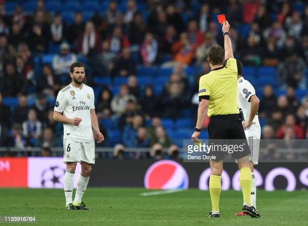 Referee Felix Brych shows the red card to Nacho of Real Madrid during the UEFA Champions League Round of 16 Second Leg match between Real Madrid and...