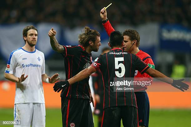 Referee Felix Brych shows the yellow card to Marco Russ of Frankfurt during the Bundesliga match between Eintracht Frankfurt and SV Darmstadt 98 at...