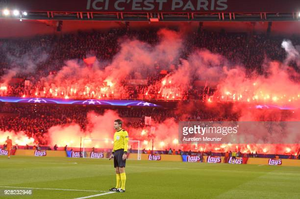 Referee Felix Brych stops the game as Paris SaintGermain fans use flares during the UEFA Champions League Round of 16 Second Leg match between Paris...