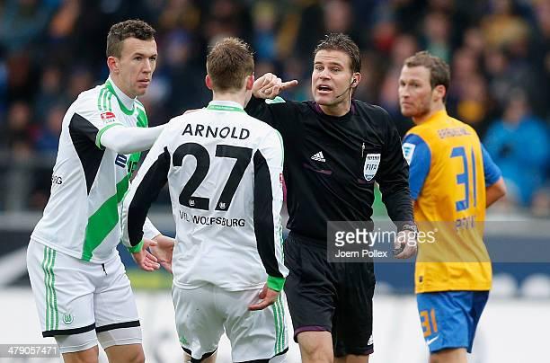 Referee Felix Brych talks to Maximilian Arnold of Wolfsburg during the Bundesliga match between Eintracht Braunschweig and VfL Wolfsburg at Eintracht...