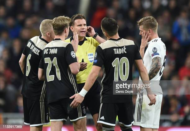 Referee Felix Brych waits for the Video Assistant Referee review before awarding Ajax their 3rd goal during the UEFA Champions League Round of 16...