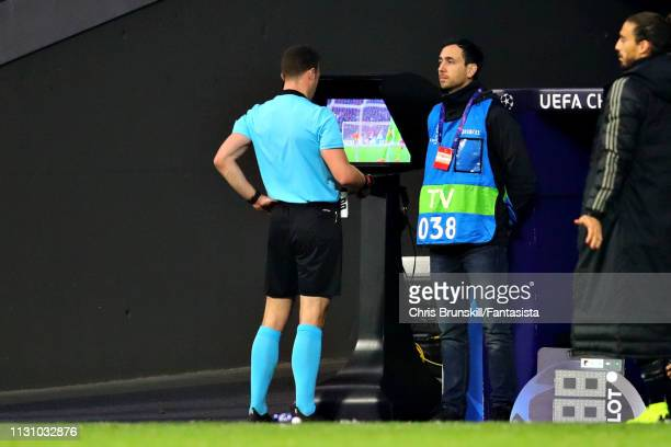 Referee Felix Zwayer checks the VAR screen during the UEFA Champions League Round of 16 First Leg match between Club Atletico de Madrid and Juventus...