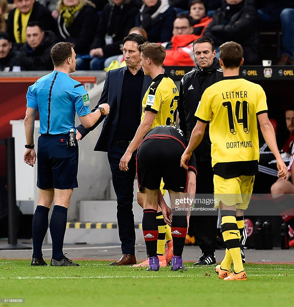 Referee Felix Zwayer exchanges words with head coach Roger Schmidt of Bayer Leverkusen during the Bundesliga match between Bayer Leverkusen and Borussia Dortmund at BayArena on February 21, 2016 in Leverkusen, Germany.