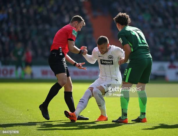 Referee Felix Zwayer helps Ante Rebic of Frankfurt with Milos Veljkovic of Bremen during the Bundesliga match between Werder Bremen and Eintracht...