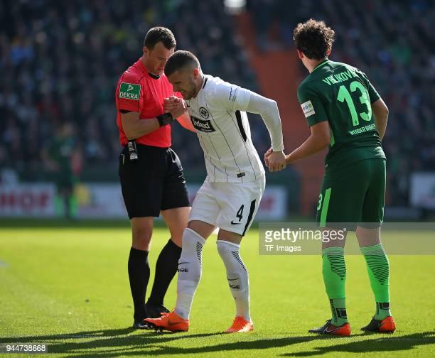 Referee Felix Zwayer hepls Ante Rebic of Frankfurt with Milos Veljkovic of Bremen during the Bundesliga match between Werder Bremen and Eintracht...