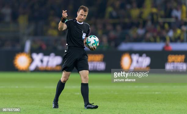 Referee Felix Zwayer holds a ball in his hand and gives instructions during the DFLSupercup match between Borussia Dortmund and Bayern Muenchen in...
