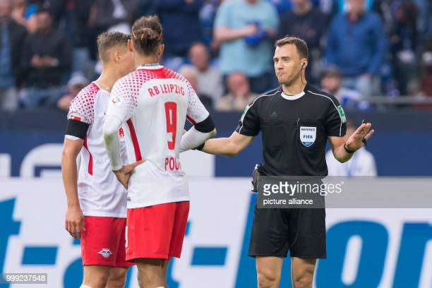 Referee Felix Zwayer justifies his decision to award Schalke a penalty which led to a 10 goal to Leipzig's Yussuf Poulsen and Leipzig's Willi Orban...