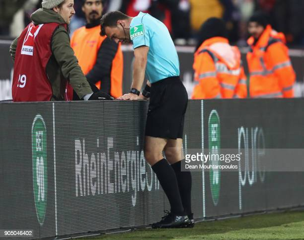 Referee Felix Zwayer looks at the TV screen for video assistant referee or VAR decision during the Bundesliga match between 1 FC Koeln and Borussia...
