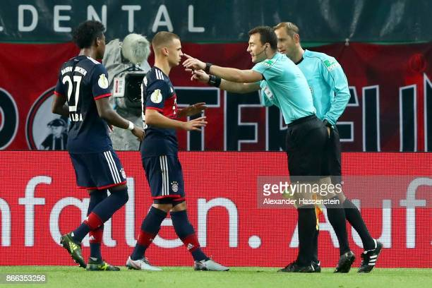 Referee Felix Zwayer reacts to David Alaba and Joshua Kimmich of Bayern Muenchen as he talks to assistent referee Thorsten Schiffner during the DFB...