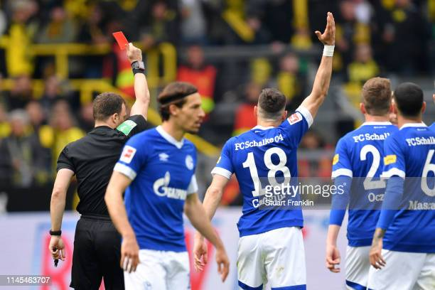 Referee Felix Zwayer shows a red card to Marco Reus of Borussia Dortmund during the Bundesliga match between Borussia Dortmund and FC Schalke 04 at...