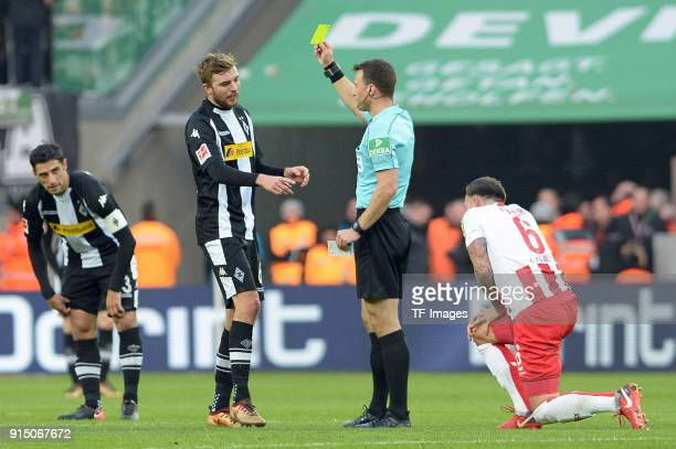 Referee Felix Zwayer shows a yellow card to Christoph Kramer of Moenchengladbach during the Bundesliga match between 1 FC Koeln and Borussia...