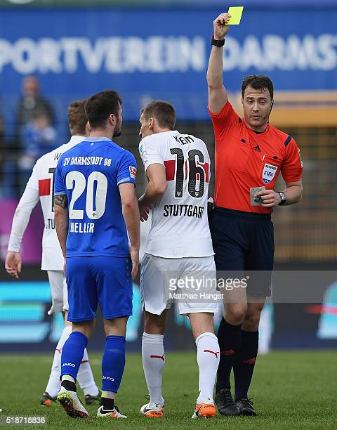 Referee Felix Zwayer shows a yellow card to Marcel Heller of Darmstadt and Florian Klein of Stuttgart during the Bundesliga match between SV...