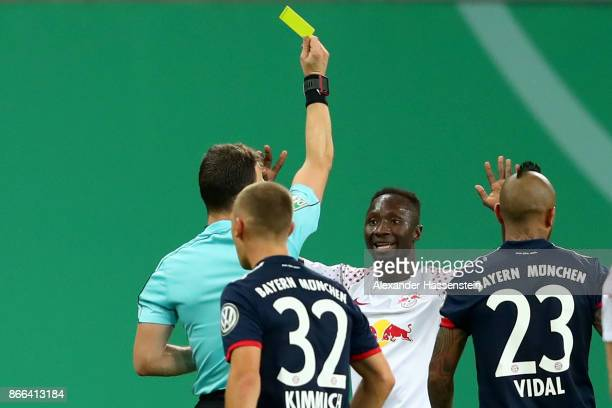 Referee Felix Zwayer shows Naby Deco Keita of Leipzig the Yellow/Red card during the DFB Cup round 2 match between RB Leipzig and Bayern Muenchen at...