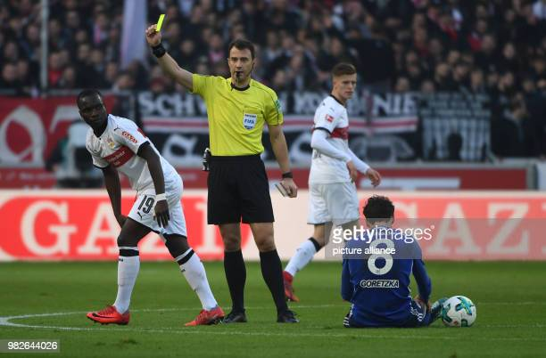 Referee Felix Zwayer shows Stuttgart's Chadrac Akolo the yellow card after a foul on Schalke's Leon Goretzka during the German Bundesliga football...