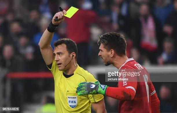 Referee Felix Zwayer shows Stuttgart's goalie RonRobert Zieler a yellow card during the German Bundesliga football match between VfB Stuttgart and FC...