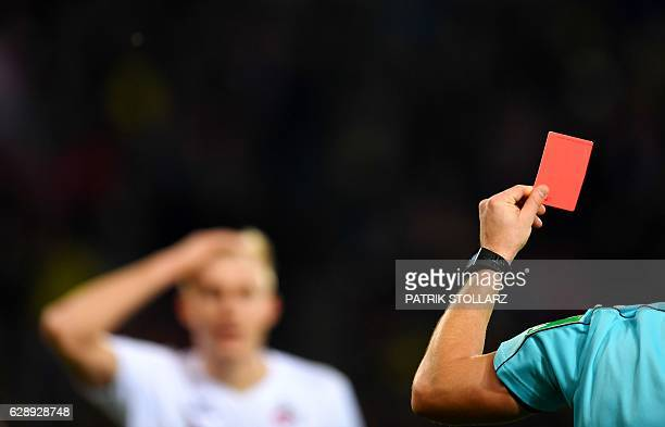 Referee Felix Zwayer shows the red card to Cologne's midfielder Salih Ozcan during the German first division Bundesliga football match between 1 FC...
