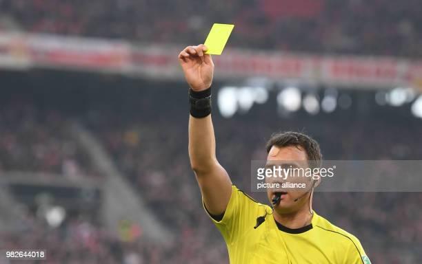 Referee Felix Zwayer shows the yellow card during the German Bundesliga football match between VfB Stuttgart and FC Schalke at the MercedesBenzArena...