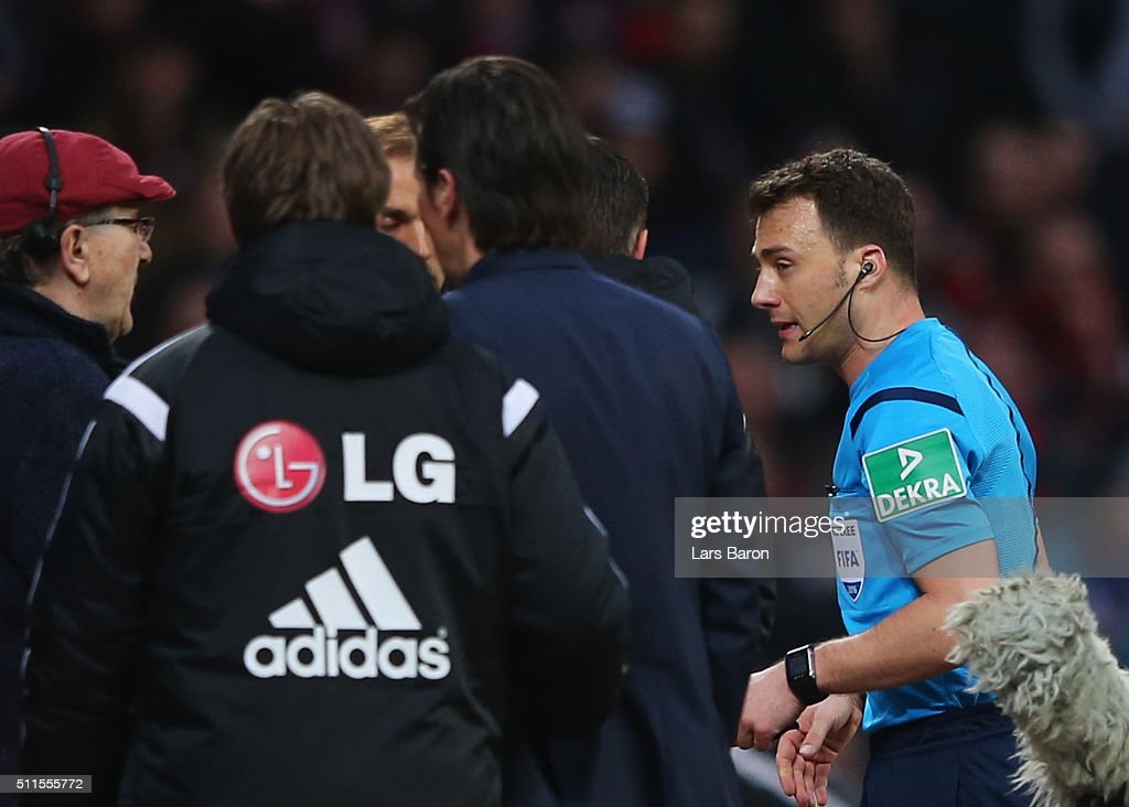 Referee Felix Zwayer walks past Roger Schmidt head coach of Bayer Leverkusen as he suspends the match after Borussia Dortmund's first goal during the Bundesliga match between Bayer Leverkusen and Borussia Dortmund at BayArena on February 21, 2016 in Leverkusen, Germany.
