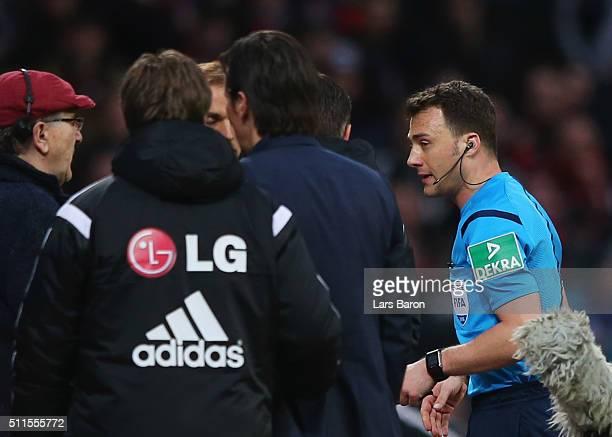 Referee Felix Zwayer walks past Roger Schmidt head coach of Bayer Leverkusen as he suspends the match after Borussia Dortmund's first goal during the...