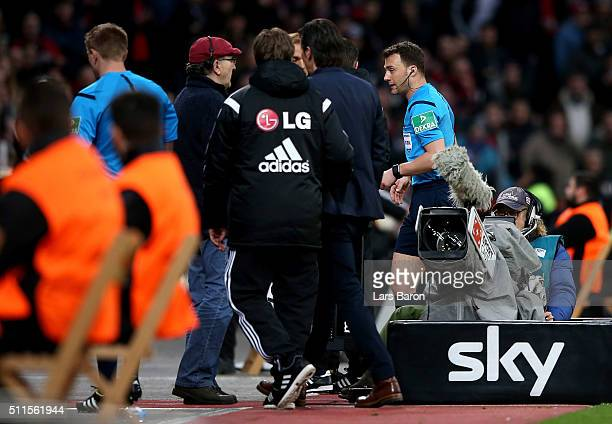 Referee Felix Zwayer walks past Roger Schmidt head coach of Bayer Leverkusen as he suspends the match after Borussia Dortmund's first goal during the...