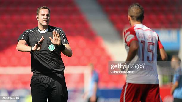 Referee Felix-Benjamin Schwermer calms down Marco Gruettner of Regensburg during the the Third League match between Jahn Regensburg and VfR Aalen at...