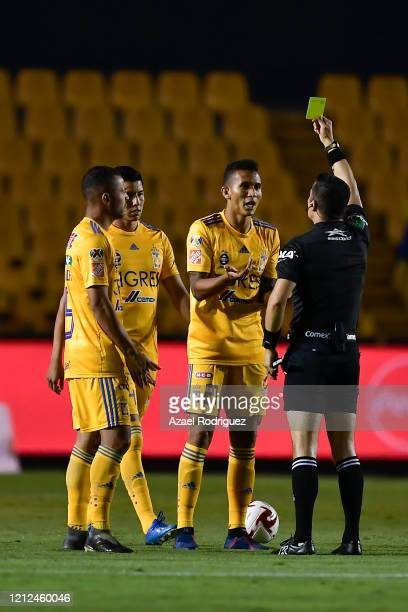 Referee Fernando Hernández gives a yellow card to Francisco Meza of Tigres during the 10th round match between Tigres UANL and FC Juarez as part of...