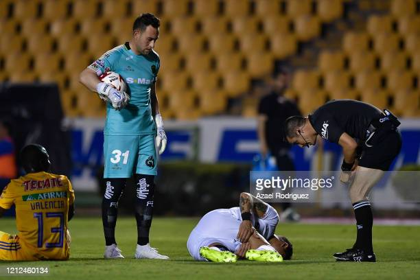 Referee Fernando Hernández talks to Bruno Romo of Juárez who lies on the ground during the 10th round match between Tigres UANL and FC Juarez as part...