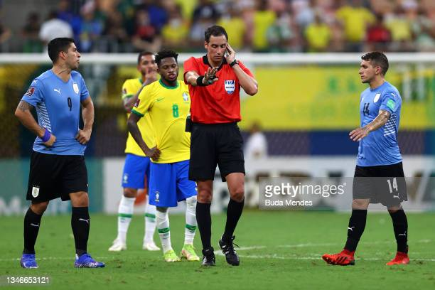 Referee Fernando Rapallini listens to the VAR to validate Brazil's fourth goal as Luis Suarez and Lucas Torreira of Uruguay react during a match...