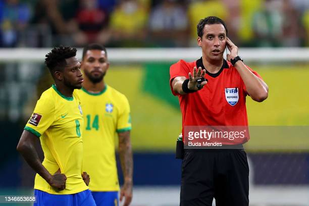 Referee Fernando Rapallini listens to the VAR to validate Brazil's fourth goal during a match between Brazil and Uruguay as part of South American...