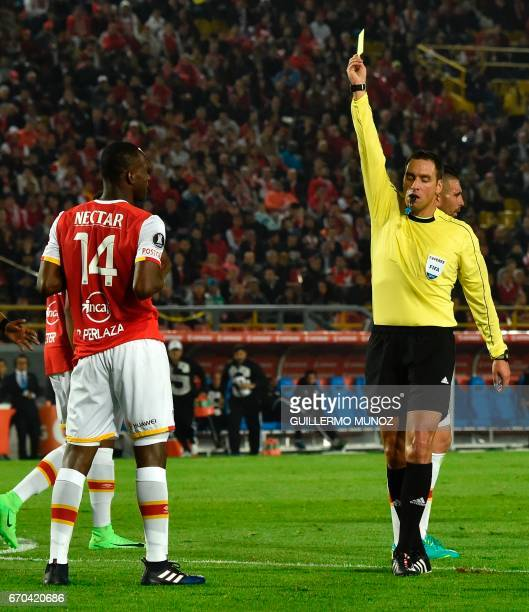 Referee Fernando Rapallini of Argentina shows the red card to Colombia´s Santa Fe player Baldomero Perlaza during the Libertadores Cup football match...