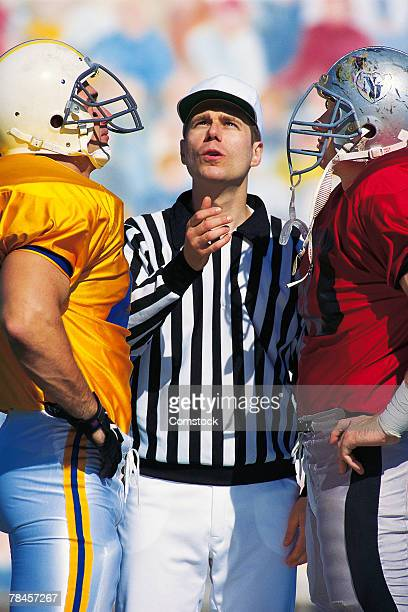 referee flipping coin at start of football game - flipping a coin stock pictures, royalty-free photos & images