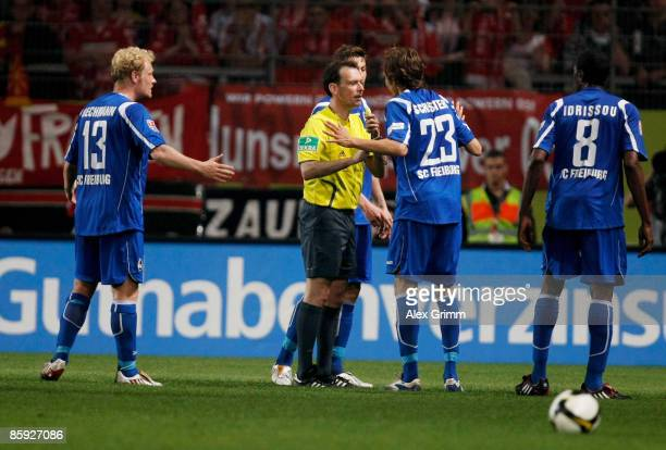 Referee Florian Meyer discusses with Tommy Bechmann Julian Schuster and Mohamadou Idrissou of Freiburg during the second Bundesliga match between FSV...