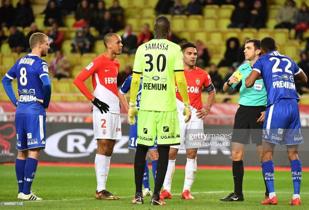 Referee Frank Schneider (2R) gives a yellow card to Troyes' French defender Christophe Herelle (R) during the French L1 football match between Monaco (ASM) and Troyes (ESTAC) at The Louis II Stadium in Monaco on December 9, 2017. /