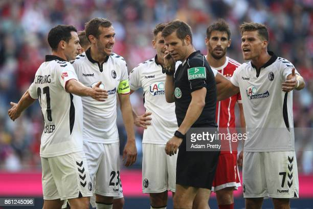 Referee Frank Willenborg listens to the video referee via his headset while players of Freiburg argue with him after awarding a penalty to Muenchen...
