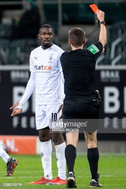 Referee Frank Willenborg shows the red card to Moenchengladbach's French forward Marcus Thuram during the German first division Bundesliga football...