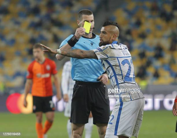 Referee from Bulgaria Georgy Kabakov shows a yellow card to Arturo Vidal of Inter during the UEFA Champions League Group B football match between...