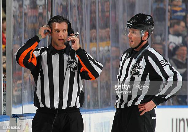 Referee Garrett Rank and linesman David Brisebois confer during a replay review in an NHL game between the Buffalo Sabres and Winnipeg Jets on March...
