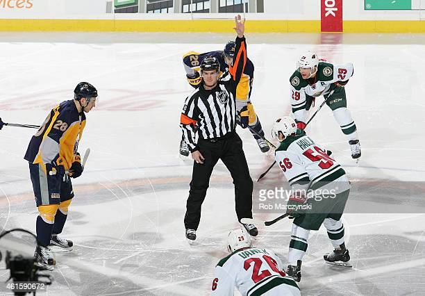 Referee Garrett Rank working his first NHL game calls players to center ice prior to dropping the puck to start the game between the Minnesota Wild...
