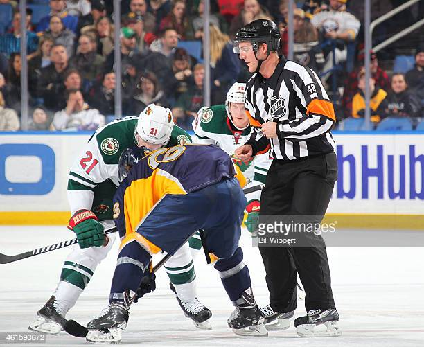 Referee Garrett Rank working his first NHL game drops the puck for a faceoff between Tyler Ennis of the Buffalo Sabres and Kyle Brodziak of the...