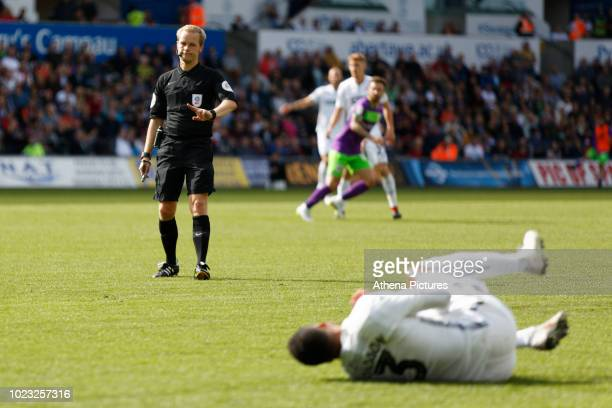 Referee Gavin Ward refuses to award a foul to Martin Olsson of Swansea City who rolls on the ground during the Sky Bet Championship match between...