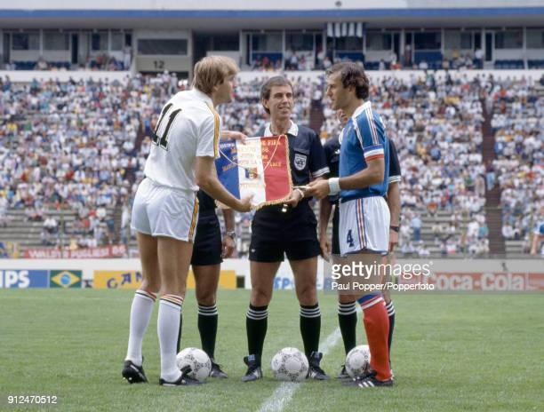 Referee George Courtney of England looks on as the captains of Belgium and France Jan Ceulemans and Patrick Battiston exchange team pennants prior to...